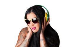 Os jovens tattooed pesadamente a mulher que escuta a cabeça do estilo do DJ Imagem de Stock