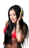 Os jovens tattooed pesadamente a mulher que escuta a cabeça do estilo do DJ Fotografia de Stock Royalty Free
