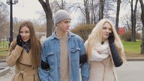 Os jovens, um indivíduo e duas meninas estão andando no parque e estão falando nos telefones Bom Sunny Day video estoque