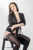 Os jovens vão vão menina com uma figura bonita em um vestido preto na moda no revestimento pele-apertado e os saltos altos e plat Fotografia de Stock Royalty Free