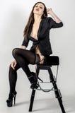 Os jovens vão vão menina com uma figura bonita em um vestido preto na moda no revestimento pele-apertado e os saltos altos e plat Foto de Stock