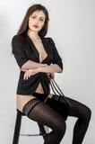 Os jovens vão vão menina com uma figura bonita em um vestido preto na moda no revestimento pele-apertado e os saltos altos e plat Fotos de Stock