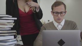 Os jovens vestiram modestamente o homem nos vidros que sentam-se na tabela em casa, trabalhando no portátil Mulher bonita com dec video estoque