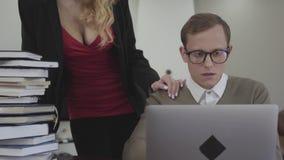 Os jovens vestiram modestamente o homem nos vidros que sentam-se na tabela em casa, trabalhando no portátil Mulher bonita com dec filme