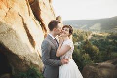 Os jovens wed recentemente pares, beijo dos noivos, abraçando na vista perfeita das montanhas, céu azul imagens de stock
