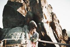 Os jovens wed recentemente pares, beijo dos noivos, abraçando na vista perfeita das montanhas, céu azul foto de stock