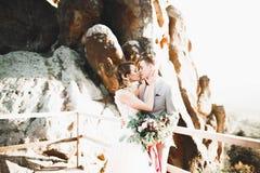 Os jovens wed recentemente pares, beijo dos noivos, abraçando na vista perfeita das montanhas, céu azul imagens de stock royalty free