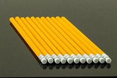 Os lápis amarelos arranjaram em uma fileira em um fundo preto De volta a Foto de Stock Royalty Free