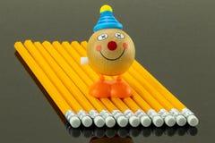 Os lápis amarelos arranjaram em uma fileira em um fundo preto e em um divertimento Fotografia de Stock Royalty Free