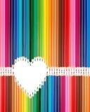 Os lápis coloridos ajustaram-se no meio da forma do coração imagens de stock