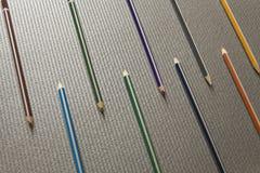 Os lápis coloridos diferentes encontram-se exatamente em um fundo plástico preto Imagem de Stock