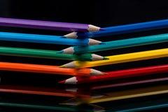 Os lápis coloridos no fundo preto refletiram na água Imagens de Stock Royalty Free