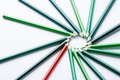 Os lápis de madeira verdes arranjam como a circular com a uma da tentativa vermelha diferente do lápis para fechar a diferença, f Foto de Stock Royalty Free