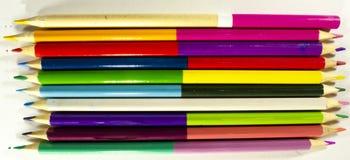 Os lápis para tirar no papel de cores diferentes encontram-se em um papel de tiragem branco fotografia de stock royalty free
