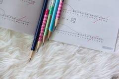 Os lápis puseram a sequência sobre o tapete branco Imagem de Stock Royalty Free