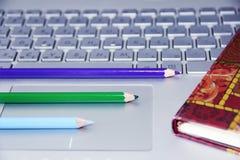 os lápis verdes e roxos azuis encontram-se em um teclado de computador de prata foto de stock