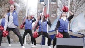 Os líder da claque atrativos nos casacos azuis executam na fase Abanadores vermelhos outdoor filme