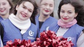 Os líder da claque atrativos nos casacos azuis sorriem in camera Abanadores vermelhos outdoor vídeos de arquivo