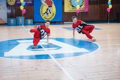 Os líder da claque novos dos meninos executam no campeonato cheerleading da cidade Fotos de Stock