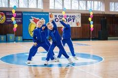 Os líder da claque novos dos meninos executam no campeonato cheerleading da cidade Imagens de Stock