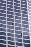 Os líquidos de limpeza de janela trabalham na construção alta da elevação Fotos de Stock Royalty Free