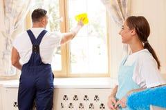 Os líquidos de limpeza novos alegres estão limpando uma casa Fotografia de Stock