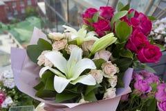 Os lírios brancos e as rosas coloridas no papel de embalagem como um presente de aniversário Imagem de Stock
