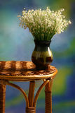 Os lírios do vale no vaso permanecem na tabela de vime Fotos de Stock Royalty Free