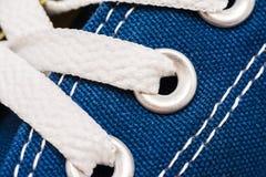 Os laços de sapata azuis das sapatilhas fecham-se acima Fotos de Stock Royalty Free