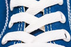 Os laços de sapata azuis das sapatilhas fecham-se acima Imagens de Stock Royalty Free