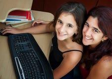 Os Lati serem de mãe e sua filha que trabalha em um computador Foto de Stock