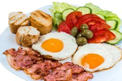 Os legumes frescos do ovo frito do café da manhã fritaram o bacon e as azeitonas em uma placa branca fotos de stock