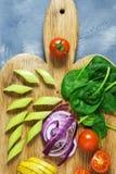 Os legumes frescos são cortados em uma placa de corte, tomates de cereja, espinafres, couve, aipo Comensal do vegetariano Vista s Fotos de Stock Royalty Free