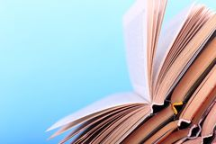 Os livros abertos são empilhados na mesa, em um fundo azul Trabalhos de casa difíceis na escola, uma montanha do conhecimento fotos de stock