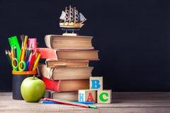 Os livros de texto e as fontes de escola velhos estão na tabela de madeira rústica em um fundo da placa de giz preta Imagens de Stock