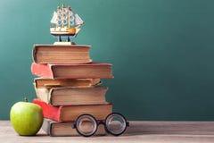 Os livros de velha escola, os livros de texto e as fontes de escola encontram-se em uma tabela de madeira Fotografia de Stock