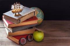 Os livros de velha escola, os livros de texto e as fontes de escola encontram-se na tabela de madeira Globo no fundo Imagens de Stock Royalty Free