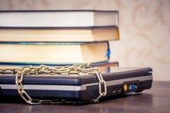 Os livros encontram-se em um portátil que seja ligado por uma corrente Livros em vez dos computadores Amor ao read_ imagens de stock royalty free
