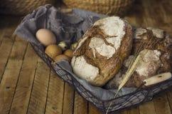 Os Loafs do pão de centeio em uma cesta com galinha eggs na tabela Foto de Stock Royalty Free