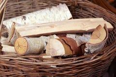 Os logs encontram-se em uma cesta de vime com um punho no fundo dos monte de feno imagem de stock