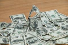 Os lotes de cem cédulas do dólar dispersaram na tabela Fotografia de Stock