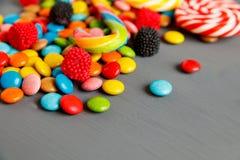 Os lotes de doces coloridos espalharam no fundo cinzento Imagem de Stock Royalty Free