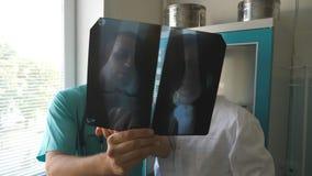 Os médicos masculinos consultam um com o otro ao olhar a imagem do raio de x Imagem caucasiano do mri da opinião de dois doutores video estoque