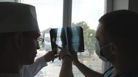 Os médicos masculinos consultam um com o otro ao olhar a imagem do raio de x Dois doutores veem a imagem do mri e a discussão sob filme