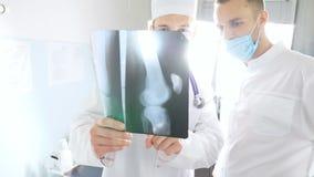Os médicos masculinos consultam um com o otro ao olhar a imagem do raio de x Os trabalhadores médicos no hospital examinam cópias filme