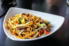 Os macarronetes chineses com cortado melhoram com legumes frescos o servido imagem de stock royalty free