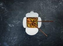 Os macarronetes da fritada da agitação do Udon com galinha em uma caixa em um vintage coloriram o fundo Vista superior Com chopst Foto de Stock Royalty Free
