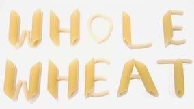 Os macarronetes soletram para fora o trigo inteiro, Inteiro-trigo no fundo branco foto de stock royalty free