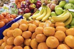 Os mandarino, bananas, maçãs encontram-se no contador do mercado para a venda imagens de stock
