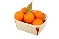 Os mandarino em uma cesta em um fundo branco Fotos de Stock Royalty Free